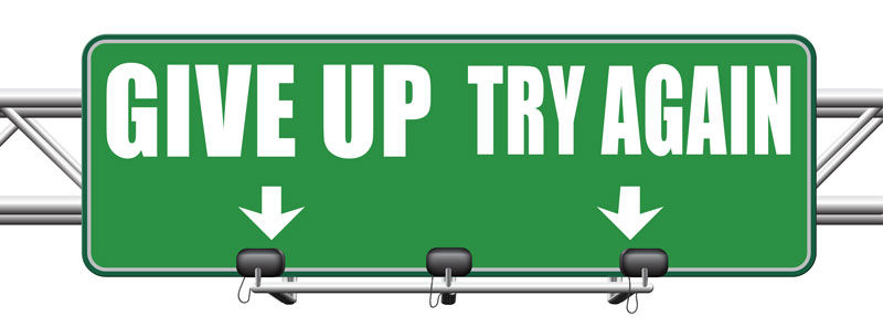 "Road sign which points in different directions, ""give up"" and ""try again"""
